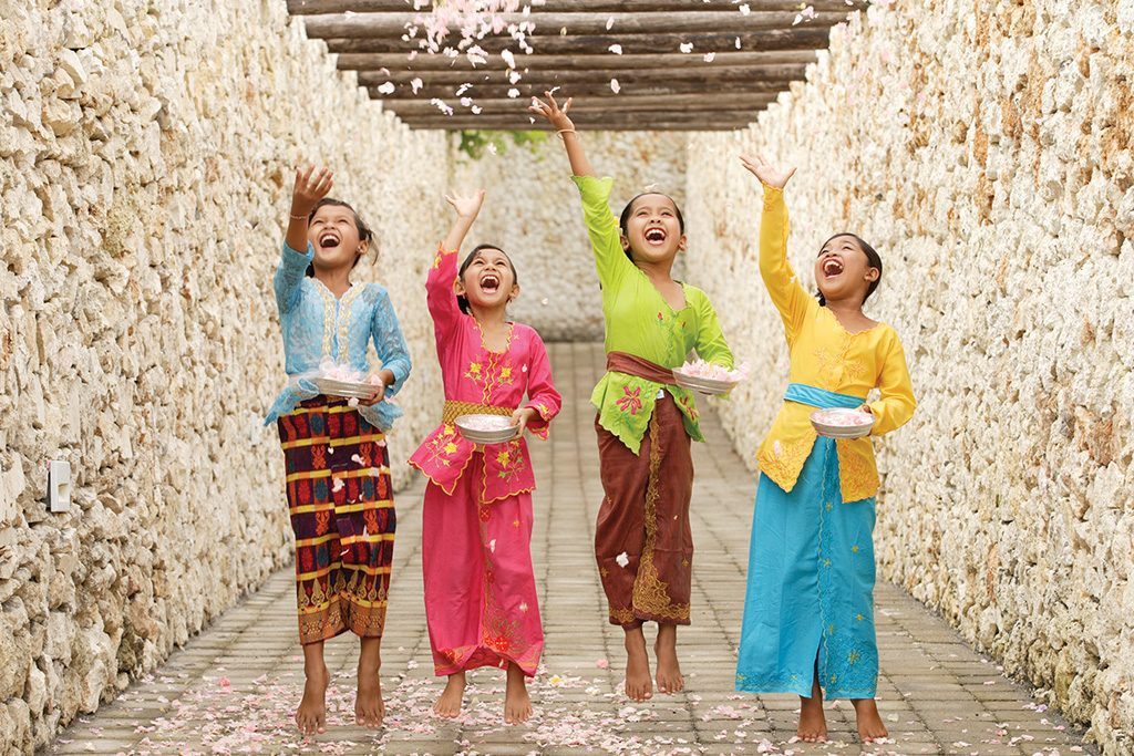 colorful Balinese kids trowing pink flower pieces happily